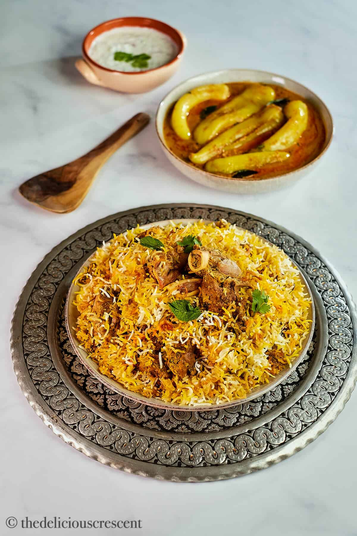 A plate full of lamb biryani served with chili pepper curry.