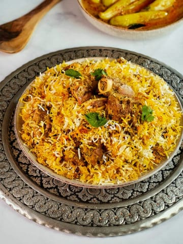 Close up view of a plate full of lamb biryani served with chili pepper curry.