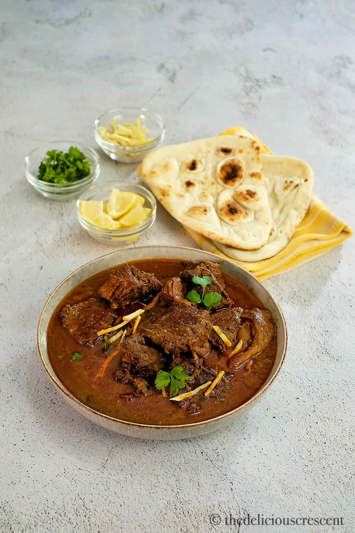 Nihari served in a dish with naan on the side.