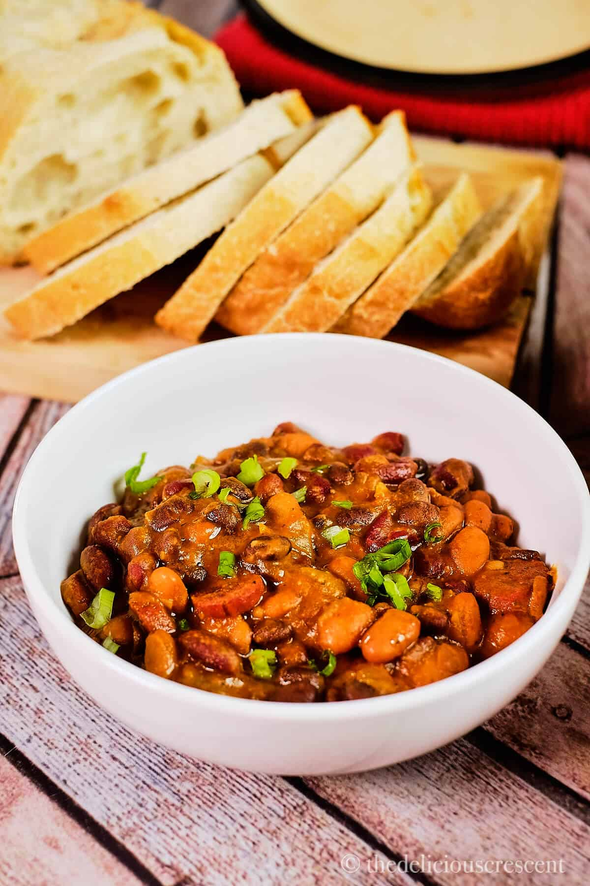 A bowl of bean and sausage stew served with bread.