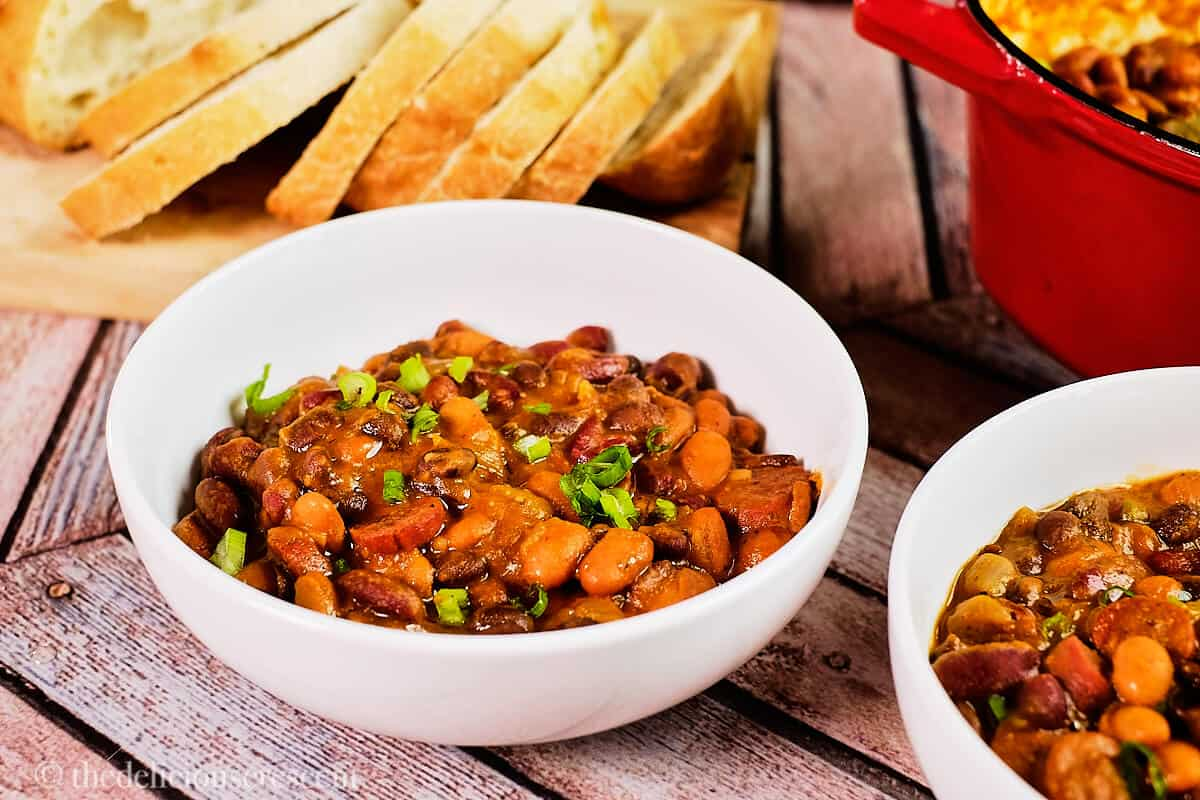 Side view of a bowl of bean and sausage stew served with bread.