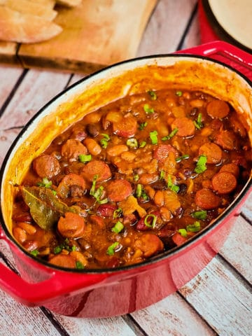 Close up view of bean stew cooked with sausage and served in a dutch oven.