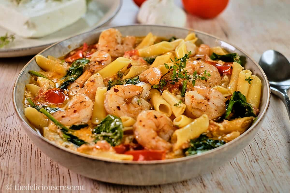 A bowl of shrimp pasta made with feta cheese sauce.